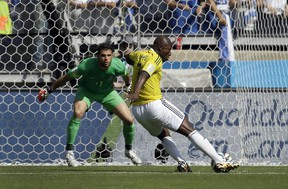 Colombia's Pablo Armero, right, kicks the ball at Greece's goalkeeper Orestis Karnezis to score his side's first goal during the group C World Cup soccer match between Colombia and Greece at the Mineirao Stadium in Belo Horizonte, Brazil, Saturday, June 14, 2014. (AP Photo/Fernando Vergara)
