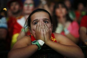 A Spanish soccer fan covers her face as she watches. . (Associated Press Photo/Andres Kudacki)