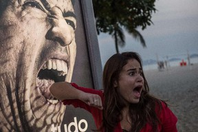 A tourist jokes in front of an advertisement with the portrait of Uruguay's forward Luis Suarez at Copacabana beach in Rio de Janeiro, Brazil, on June 26, 2014. Sportswear giant Adidas said Thursday it would stop using Luis Suarez, one of its key promotional stars, for World Cup adverts after his four-month ban from football activities for biting Italian Giorgio Chiellini. YASUYOSHI CHIBA/AFP/Getty Images
