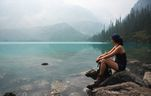 A woman looks out onto the water at Joffre Lakes Provincial Park.