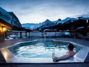 A man relaxes in a hot tub at Deer Lodge in Lake Louise Alberta