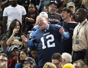 """Toronto Mayor Rob Ford laughs with fans as he attends the Toronto Argonauts and Hamilton Tiger-Cats CFL Eastern Conference final football game in Toronto on Sunday, Nov. 17, 2013. A quartet of self-described """"knuckleheads"""" celebrated a journalistic touchdown Thursday as they nabbed a timely, unexpected interview with Ford.THE CANADIAN PRESS/Nathan Denette"""