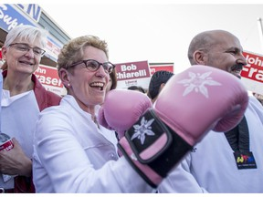 Ontario Liberal leader Kathleen Wynne shows off a pair of boxing gloves she received as a gift, while her partner Jane Rounthwaite (left) looks on, during a campaign stop in Ottawa South, the riding of John Fraser (right) and former riding of Premier Dalton McGuinty, in Ottawa on Wednesday, May 7, 2014.