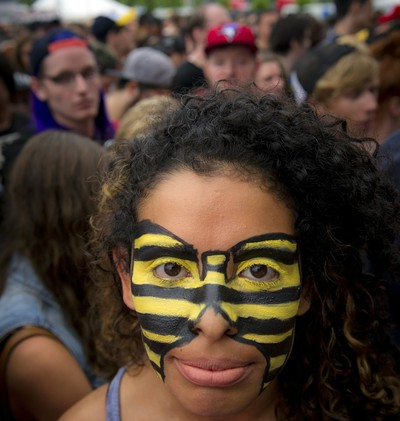 """A fan's face is painted with the """"killer bee"""" colours of the Wu-Tang Clan, the hip hop crew that drew a huge crowd at Bluesfest in 2013.(Photo by Ashley Fraser, Ottawa Citizen)"""