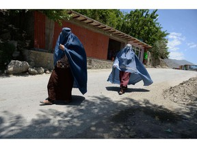 This file photograph taken on June 8, 2014 shows two burqa-clad Afghan women making their way in Bazarak district, Panjshir province. Getty photo.
