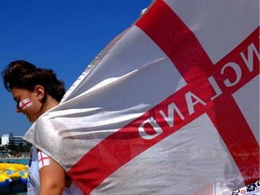 "An English soccer fan in Cyprus holds an England flag on ""Nissi Beach"" in the famous southeastern coastal resort of Ayia Napa, Cyprus, Saturday, June 14, 2014.  England will play today against Italy in 2014 World Cup in Brazil."