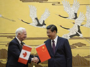 Chinese President  Xi Jinping (R) welcomes Governor General David Johnston of Canada at the Great Hall of the People on October 18, 2013 in Beijing, China.