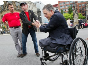Major Mark Campbell (Ret'd) (R) who lost his legs to an IED in Afghanistan is greeted by supporters including Ken Anson (L) as 'Rock the Hill' takes place on Parliament Hill with veterans, families and supporters hoping to draw attention to the problems Canadian veterans are facing. Photo taken at 14:24 on June 4, 2014.