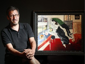 Saw Gallery curator, Jason St-Laurent, sits beside a painting in the style of Marc Chagall by Graciela Montealegre.