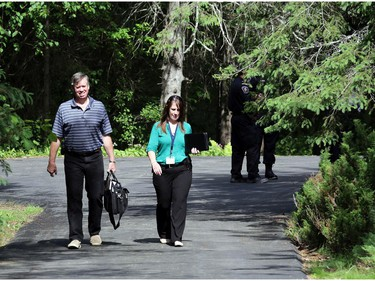 The coroner (left) and a police investigator leave the scene of a fire and death at 170 Grey Fox Dr. in Corkery (Ottawa), Sunday, June 8, 2014.