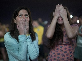 Brazil soccer fans react as they watch their team lose a World Cup semi-final match against Germany, on Copacabana beach in Rio de Janeiro, Brazil, Tuesday, July 8, 2014. Germany poured in the goals Tuesday to hand Brazil its heaviest World Cup loss ever with an astounding 7-1 rout in the semifinals that stunned the host nation.