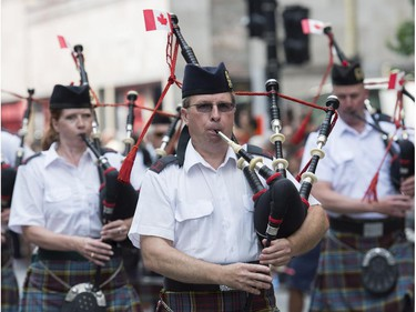 A piped band entertains the crowd during the annual Canada Day parade in Montreal, Tuesday, July 1, 2014.