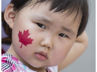 A young girl enjoys the festivities during the annual Canada Day parade in Montreal, Tuesday, July 1, 2014.