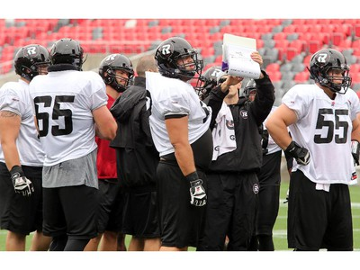 """Hello?"" It looks as if very few of the players are paying attention as a playbook is gone over with some of the offensive linemen as the Ottawa Redblacks practice through a downpour Tuesday morning at TD Place Stadium at Lansdowne Park."
