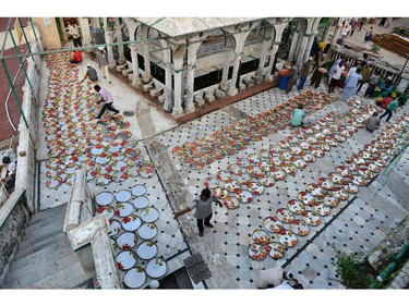 Indian Muslims lay out food for Iftar, the breaking of fast during Ramadan at the Alif Ni Masjid in Ahmedabad on July 27, 2014.   The Iftar, for people who come to shop in the Teen Darwaja area of Ahmedabad, was organised by the Khwaja Garib Nawaz Khidmat Patharna Bazar.  Across the Muslim world, the faithful fast from dawn to dusk and abstain from eating, drinking, smoking and having sex during the Holy Month of Ramadan as they strive to be more pious and charitable.