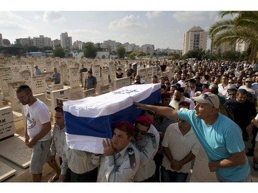 Israeli soldiers carry the coffin of Warrant Officer Rami Cahlon during his funeral at the military cemetery in Hadera, northern Israel, Sunday, July 27, 2014. Cahlon was injured during fighting in Gaza and died from his wounds four days later.