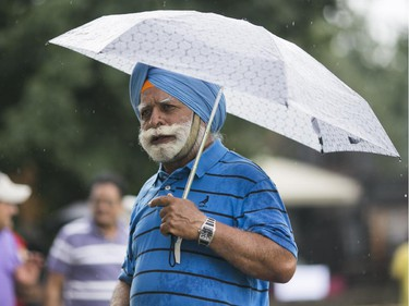 Mahan Sings shelters himself from the rain during a picnic at Saunders Farm. Hundreds of people from the Ottawa indian community took part in the India Canada Association: Unity Picnic at Saunders Farm in Munster, July 27, 2014.        (Chris Roussakis/Ottawa Citizen)