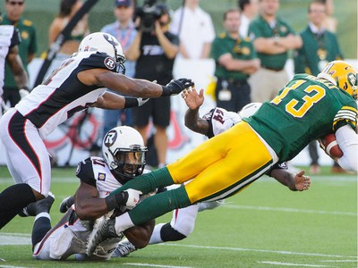Mike Reilly #13 of the Edmonton Eskimos runs the ball for first down against the Ottawa Redblacks during a CFL game at Commonwealth Stadium on July 11, 2014 in Edmonton, Alberta, Canada.