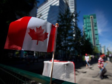 A Canadian flag is seen on a fence as people play ball hockey during Canada Day celebrations in Vancouver, B.C., on Tuesday July 1, 2014.