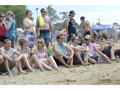 People take in the scene at the HOPE Volleyball Summerfest at Mooney's Bay Beach in Ottawa on Saturday, July 12, 2014.