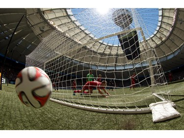 The ball bounces behind the goal off a Vancouver Whitecaps shot that went wide as FC Dallas' Walker Zimmerman, centre, dives across the goal line while goalkeeper Raul Fernandez, back, of Peru, watches during the first half of an MLS soccer game in Vancouver, B.C., on Sunday July 27, 2014.