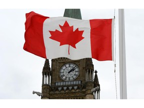A Canadian flag blows in front of the Peace Tower on Parliament Hill.