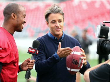Ben Mulroney, from E talk, interviews QB Henry Burris and gets a few tips on how to throw a ball.  Ottawa Redblacks run through a light practice Thursday, August 14, 2014 at TD Place stadium before Friday night's home game against the Edmonton Eskimos.