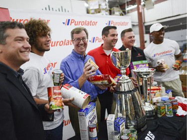 (L-R) Ottawa City Councillor Tim Tierney, Fury FC forwards, Tom Heinemann, Mayor Jim Watson, Manager of corporate sponsorship from Purolator, Brian Collins, Executive director at the Ottawa Food Bank, Michael Maidment, and The Ottawa  Redblacks QB, Henry Burris smiles for the camera at the Ottawa Food Bank for Purolator Tackle Hunger weekend on Thursday, Aug. 14, 2014.  Fans attending the Redblacks and Fury FC games in Aug. 15 and 17 are encouraged to bring non-perishable food items or cash donations to the volunteers stationed at the stadium gates. Fans will have the opportunity to have a photo taken with the Grey Cup and North American Soccer League (NASL) Soccer Bowl trophy.