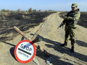A Ukrainian serviceman stands guard at a Ukrainian National Guard position on the border checkpoint near Novoazovsk, Donetsk region after a multiple launch rocket systems and the cannon were allegedly fired from the Russian Federation territory on Aug. 23, 2014.