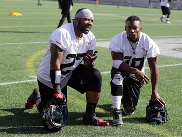 Ottawa RedBlacks running backs (L2R) Jeremiah Johnson (27) and Roy Finch (19) take a breather after practice today at TD Place in Ottawa, Monday, October 27, 2014. The RedBlacks take on Hamilton Tiger-Cats this Friday at TD Place.