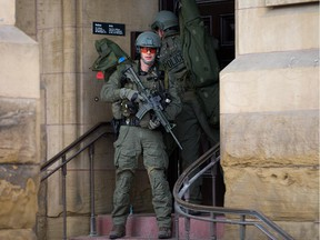 RCMP tactical officers attempt to enter the Langevin Block as police respond to an apparent terrorist attack in Ottawa.