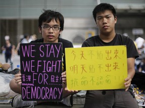 Student protesters sit with signs on their fight for democracy in Hong Kong Wednesday, Oct. 1, 2014.