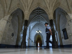 A security guard walks past the Hall of Honour in Centre Block on Parliament Hill in Ottawa on Thursday October 23, 2014. The House of Commons is back in action, kicked off by an exhilarating show of support for the sergeant-at-arms of the House of Commons, who was among those who opened fire Wednesday on the gunman who stormed Parliament Hill.