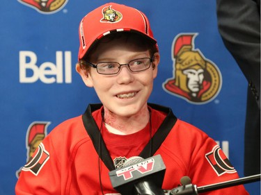 Late general manager of the Ottawa Senators, Bryan Murray, Pierre Dorion and Randy Lee, sign Jonathan Pitre as a pro scout for one day at the Canadian Tire Centre in Ottawa, November 20, 2014.