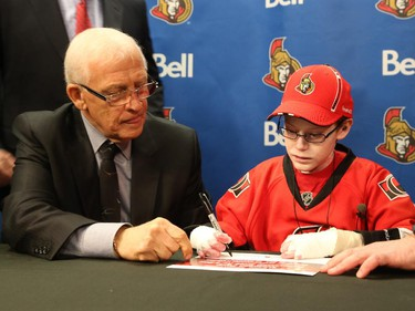 General manager of the Ottawa Senators, Bryan Murray, left, signs Jonathan Pitre as a pro scout for one day.