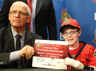 Late general manager of the Ottawa Senators, Bryan Murray signs Jonathan Pitre as a pro scout for one day at the Canadian Tire Centre in Ottawa, November 20, 2014.