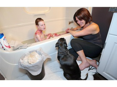 Molly, the family's other Pug/Terrier mix, lightens the mood at bath time.