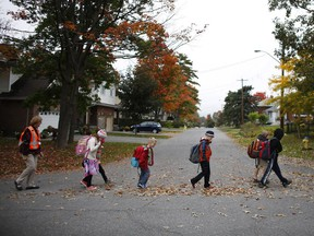 The walking school bus, a pilot project where paid adults walk large numbers of kids to school, makes its way to Woodroffe Public School on Sept. 30, 2014. (David Kawai / Ottawa Citizen)