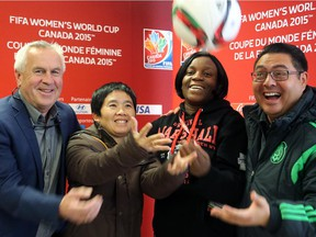 From left, Even Pellerud, head coach of Norway's women's soccer team; Thailand's coach, Nuengrutai Srathongvian;  Ivory Coast's coach,  Clementine Toure, and team manager for Mexico's women's national soccer team, Gerardo Lepe, toss a soccer ball in the air at a press availability session the R.A. Centre in Ottawa.