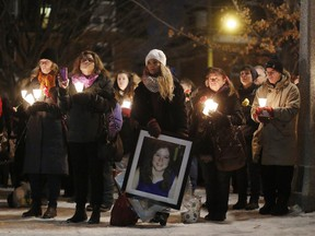Kimberly Scobie, holding a portrait of Donna Jones, who was murdered by her husband five years ago, was among the dozens who gathered at the Women's Monument in Minto Park for a candlelight vigil to commemorate the lives of women killed due to male violence. This year marks the 25th anniversary of the Montreal Massacre, where 14 women were killed at the Ecole Polytechnique.