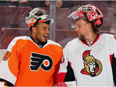 Ray Emery #29 of the Philadelphia Flyers shares a laugh with Robin Leher #40 of the Ottawa Senators during warmups.