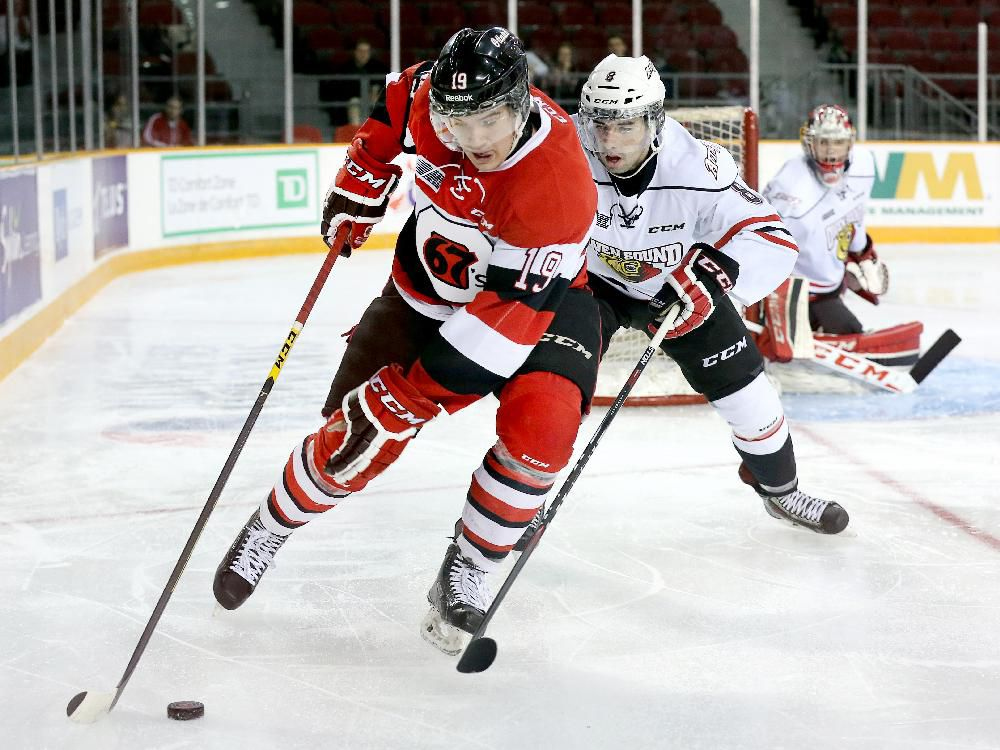 Travis Barron (L) holds Santino Centorame (C) off the puck while goalie Jack Finn looks on in the first period as the Ottawa 67s take on the Owen Sound Attack in OHL action at TD Place Arena on Friday evening.