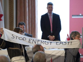Standing on stage, Energy East Pipeline President François Poirier watches as protesters hold a banner in front of the podium during his speech to the Canadian Club of Canada during a luncheon in Ottawa, Monday, Feb. 2, 2015.