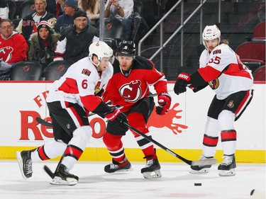 Dainius Zubrus #8 of the New Jersey Devils battles for the puck against Bobby Ryan #6 and Erik Karlsson #65 of the Ottawa Senators.