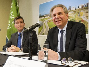 The National Capital Commission's Pierre Lanctot, executive director of corporate services, left, looks on as Mark Kristmanson, NCC CEO, speaks during a press conference to announce the shortlist of developers for Lebreton Flats Wednesday February 18, 2015. (Darren Brown/Ottawa Citizen)