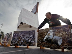 A volunteer of the non-governmental organization Handicap International places a picture, showing a cluster bomb in Lebanon, during an action supporting a cluster bomb ban on November 3, 2008 in front of the United Nations offices in Geneva.