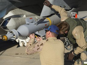 An Air Weapons Systems Technician and a pilot inspect a CF-18 Hornet fighter jet before the next mission at Camp Patrice Vincent during Operation Impact on January 14, 2015.