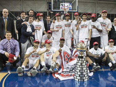 Carleton Ravens pose with the trophy after defeating the Ottawa Gee-Gees to win the CIS basketball final action in Toronto on Sunday, March 15, 2015.