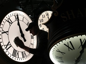 Dave LeMote wipes down a post clock at Electric Time Company, Inc. in Medfield, Mass., Friday, March 7, 2014.