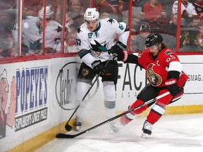 Erik Karlsson #65 of the Ottawa Senators and Tommy Wingels #57 of the San Jose Sharks dig for a loose puck along the boards.